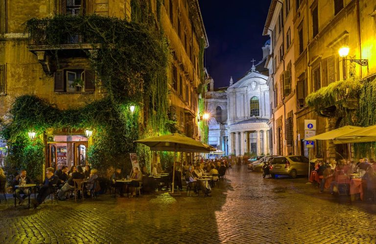 People sat at restaurants in Rome at night time
