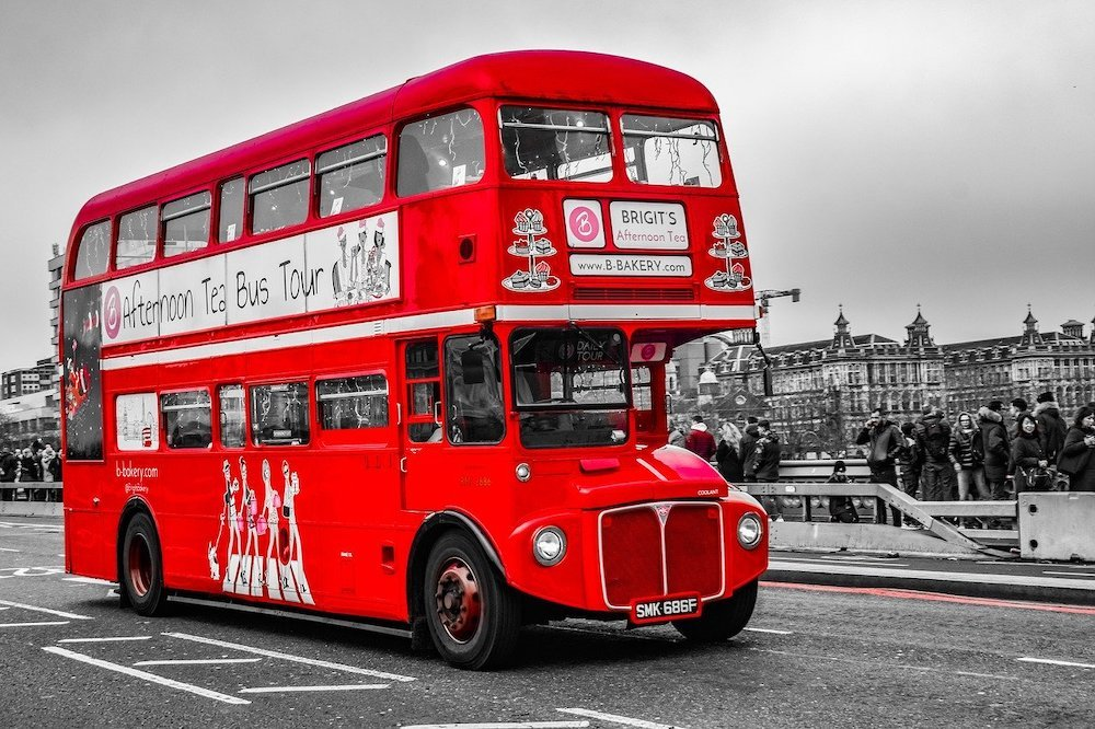 Red London bus in a black and white image