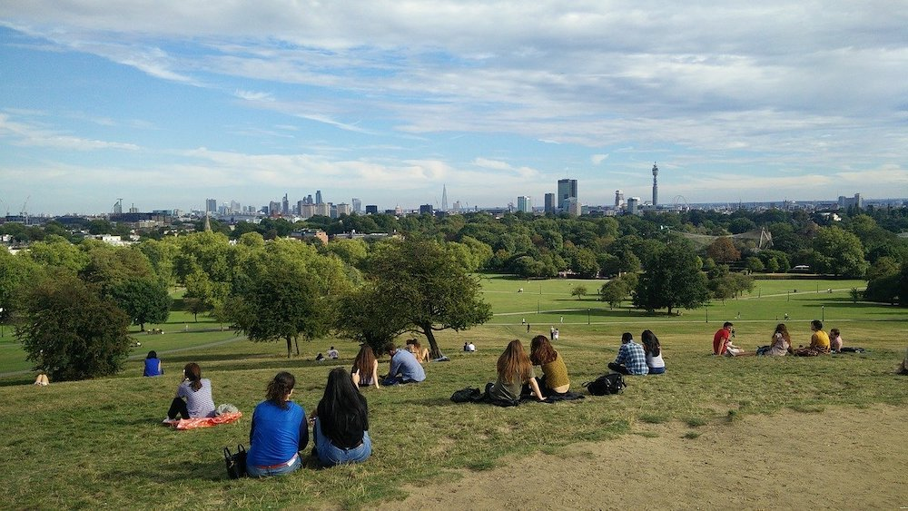 People sitting admiring the view of London from Primrose Hill
