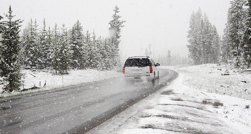 Car driving on a road surrounding by snowy grass and trees